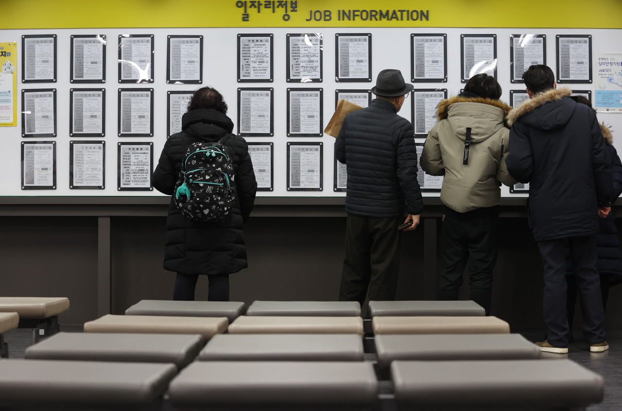 This file photo, taken Jan. 13, 2021, shows people looking at job opening information at an employment arrangement center in Seoul. (Yonhap)