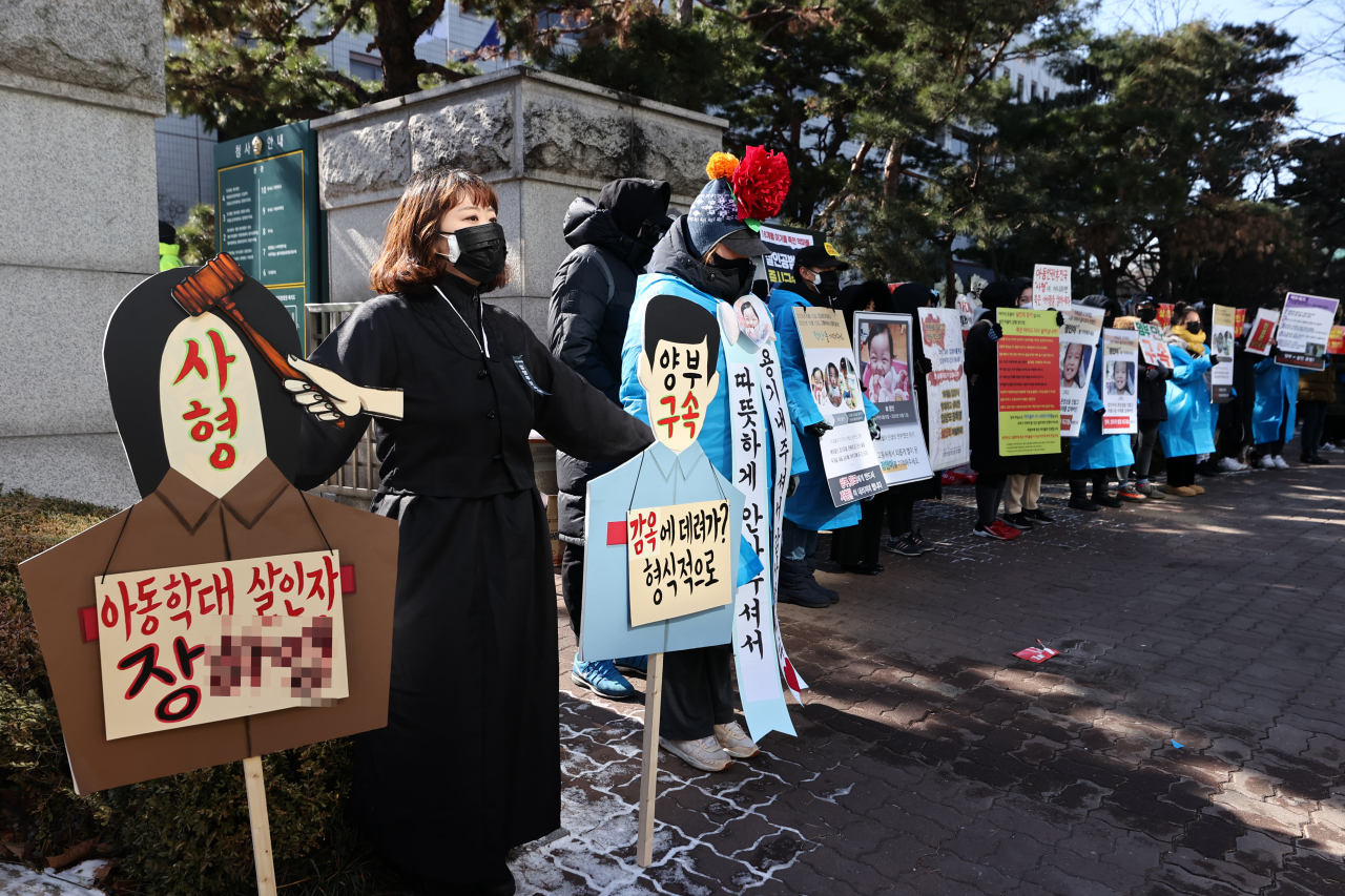 This Feb. 17, 2021, file photo shows people calling for stern punishment against two parents, who allegedly abused their 16-month-old adopted daughter to death in October, in front of the Seoul Southern District Court. (Yonhap)