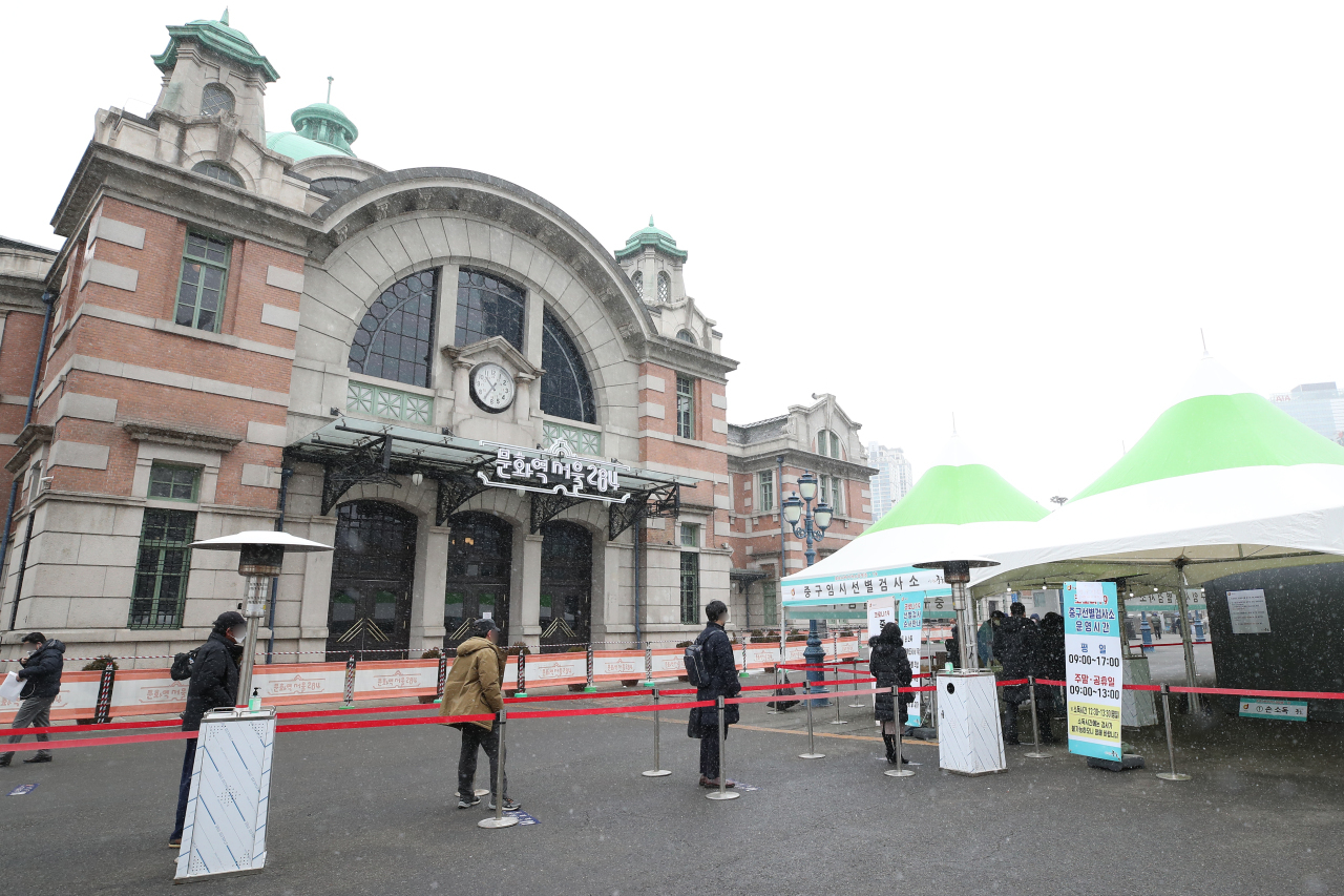 People stand in line to get COVID-19 testing at a temporary screening station in front of Seoul Station last Tuesday. (Yonhap)