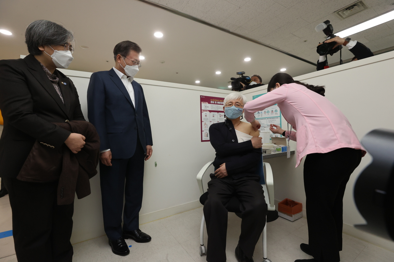 Kim Yoon-tae, a doctor at a children's hospital, receives a COVID-19 vaccination at a public health center in Mapo, western Seoul, Friday as President Moon Jae-in and Korea Disease Control and Prevention Agency Commissioner Jeong Eun-kyeong watch the process. (Yonhap)