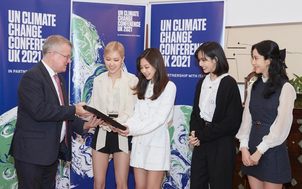This photo, provided by YG Entertainment, shows BLACKPINK receiving a letter from Simon Smith, British ambassador to South Korea, during an event at the British Embassy in Seoul. (YG Entertainment)