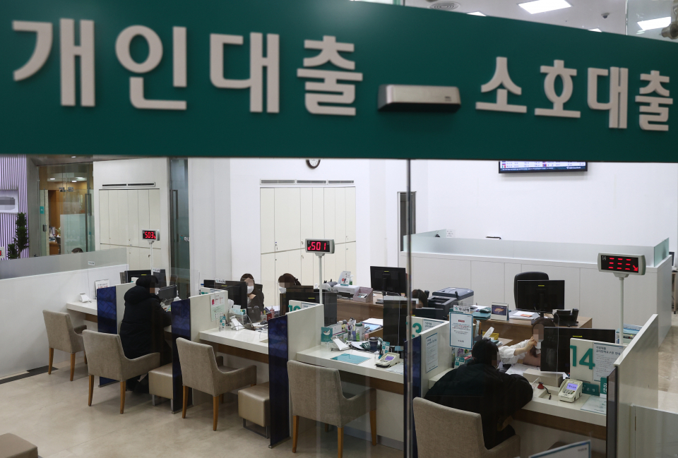 This file photo, taken on Jan. 5, 2021, shows customers consulting about loan products at a bank in Seoul. (Yonhap)