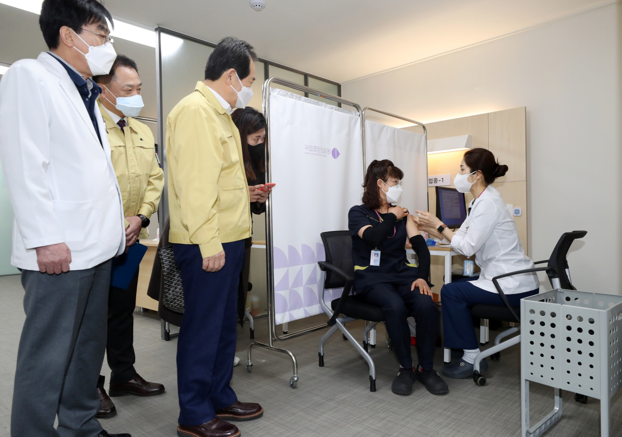 Chung Mi-kyeong (second from right), a sanitation worker of the National Medical Center, receives a Pfizer vaccine at the hospital in central Seoul on Saturday, while Prime Minister Chung Sye-kyun (third from left) looks on. She became the first South Korean to get the Pfizer product. (Yonhap)