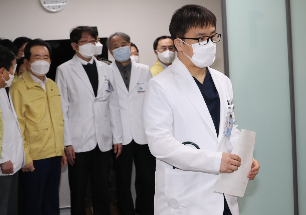 A doctor (right) at the National Medical Center in central Seoul waits to receive the first shot of Pfizer's COVID-19 vaccine as a medical worker on Saturday. (Yonhap)