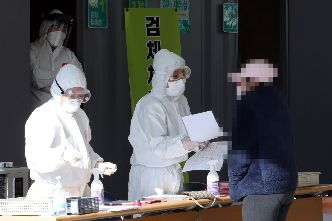 A foreign national (right) waits to get a coronavirus test at a temporary testing station in Naju, South Jeolla Province on Feb. 4. (Yonhap)