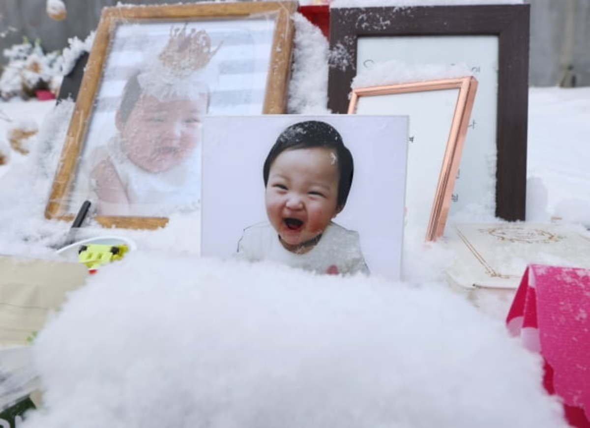 This Jan. 13, 2021, file photo shows pictures of a 16-month-old toddler, named Jung-in, who died in October allegedly as a result of her adoptive parents' abuse. (Yonhap)