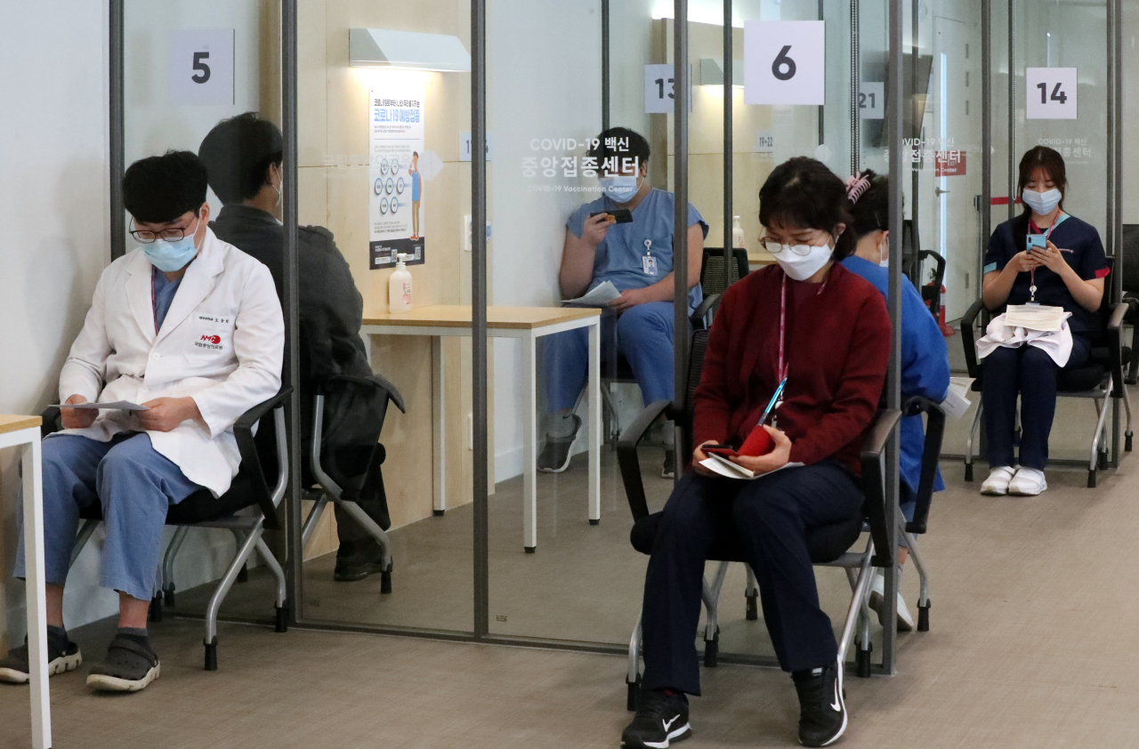 Medical workers wait in an observation area after receiving Pfizer's COVID-19 vaccine at a hospital in central Seoul on Saturday. (Yonhap)