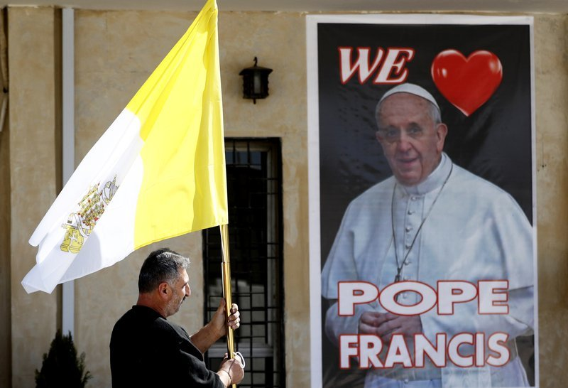 A Christian priest holds a Vatican flag as he walks by a poster of Pope Francis during preparations for the Pope's visit in Mar Youssif Church in Baghdad, Iraq, Friday. (AP-Yonhap)