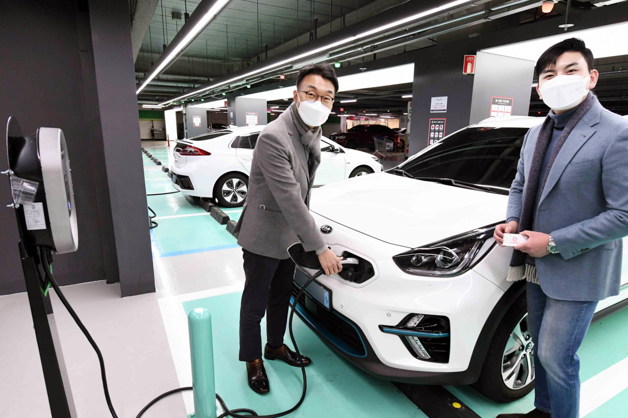 Officials are charging an electric vehicle from an EV charger installed at Homeplus Gangseo branch in Seoul. (Homeplus)