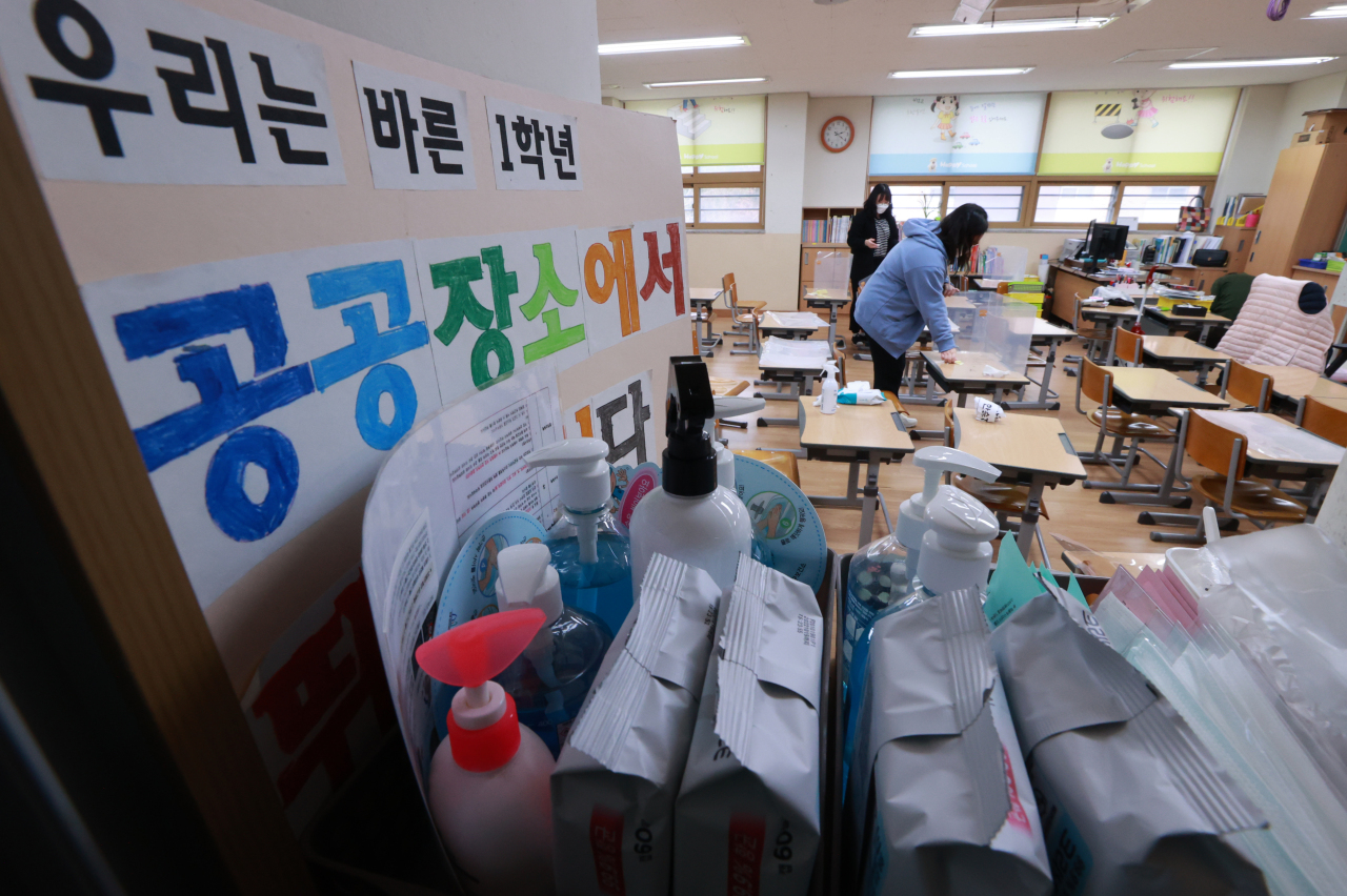 School officials prepare a classroom for students in Seoul last Thursday. (Yonhap)