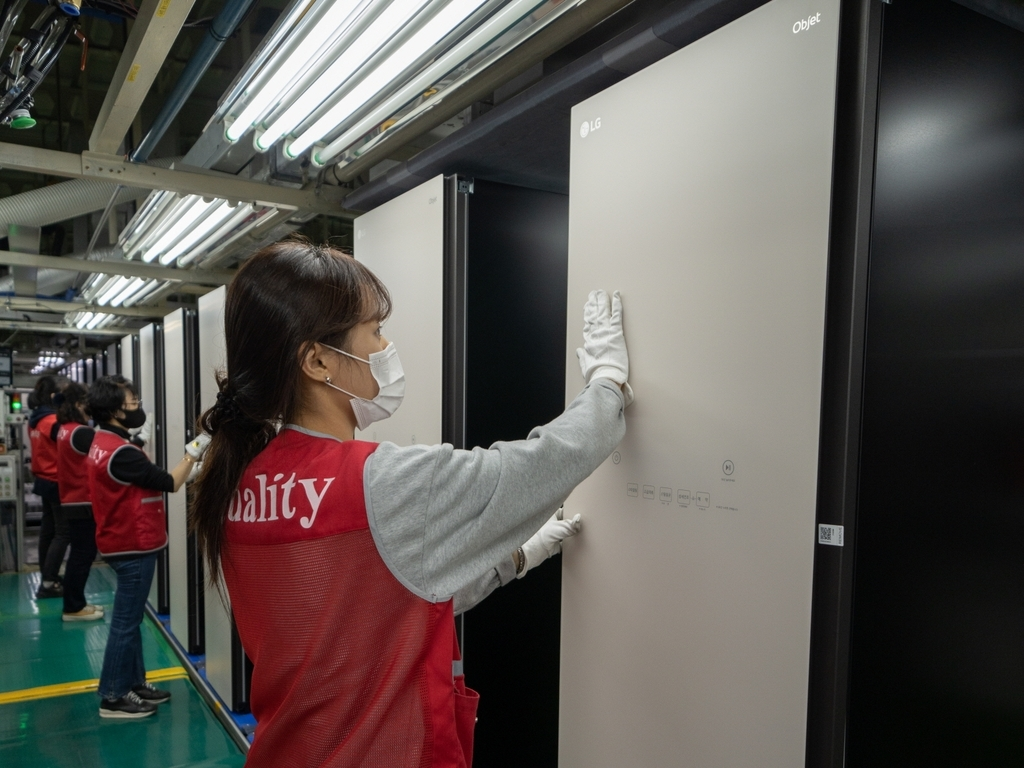 This photo provided by LG Electronics Inc. on Tuesday, shows a worker checking the Styler steam clothing care appliance at the company's plant in Changwon, some 400 kilometers south of Seoul. (LG Electronics Inc.)