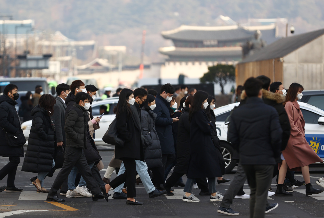 People cross the street near Gwanghwamun area in central Seoul on Wednesday morning to report to work. (Yonhap)