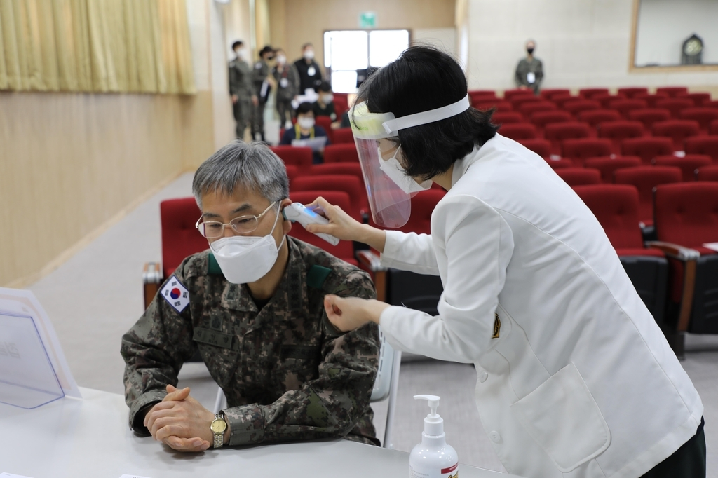 Col. Kim In-young (L), who is the chief of the Korean Armed Forces Yangju Hospital in Gyeonggi Province, has his temperature checked ahead of receiving the COVID-19 vaccine on Wednesday, in this photo provided by the defense ministry. (Ministry of National Defense)