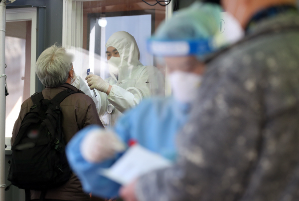 This file photo taken on Wednesday, shows a health worker clad in a protective suit collecting a sample from a citizen at a makeshift virus clinic in Seoul. (Yonhap)