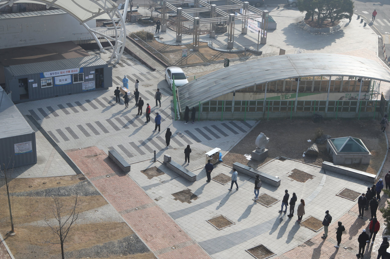 Citizens form a long line to receive tests at an outdoor COVID-19 testing station in Dongducheon, 40 km north of Seoul, on Wednesday. (Yonhap)