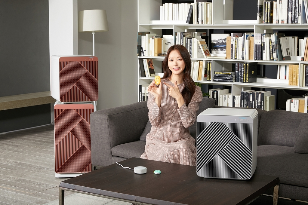 This photo provided by Samsung Electronics Co. on Thursday, shows a model introducing Kakao Enterprise Corp.'s smart speakers and Samsung's air purifier at a studio in Suwon, south of Seoul. (Samsung Electronics Co.)