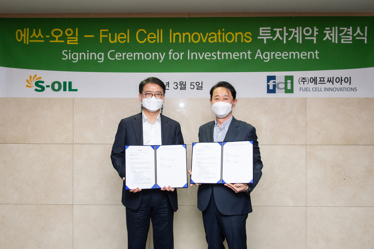 S-Oil President Ryu Yul (left) and FCI CEO Lee Tae-won pose for a photo after signing an investment agreement at S-Oil headquarters in Mapo-gu, western Seoul, Friday. (S-Oil)