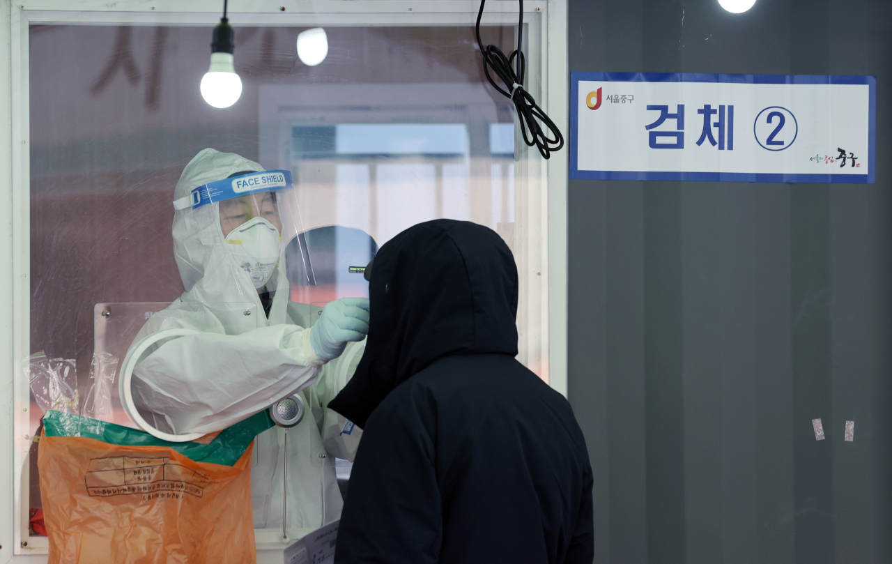 A medical worker takes sample from a person in line for COVID-19 check at a temporary diagnostic center made near Seoul Station on Sunday. (Yonhap)
