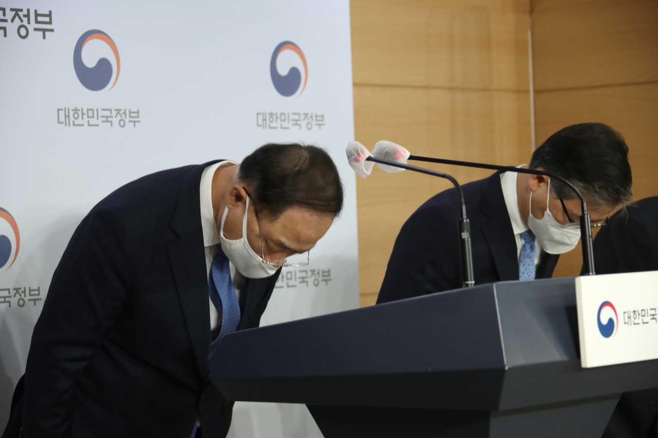 Finance Minister and Deputy Prime Minister Hong Nam-ki (left) bows his head in apology over the latest scandal involving alleged speculative purchases of land lots by officials at the Korea Land & Housing Corp., following a meeting of real estate policy-related ministers held at the Seoul government complex on Sunday. (Yonhap)