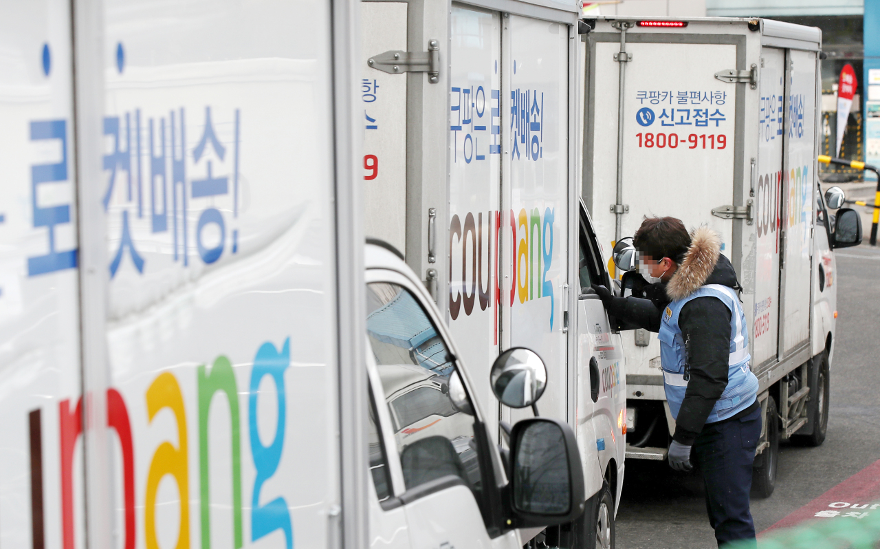 This file photo shows South Korean e-commerce giant Coupang Corp.'s delivery trucks leaving a logistics center in southern Seoul on Feb. 16, 2021. (Yonhap)