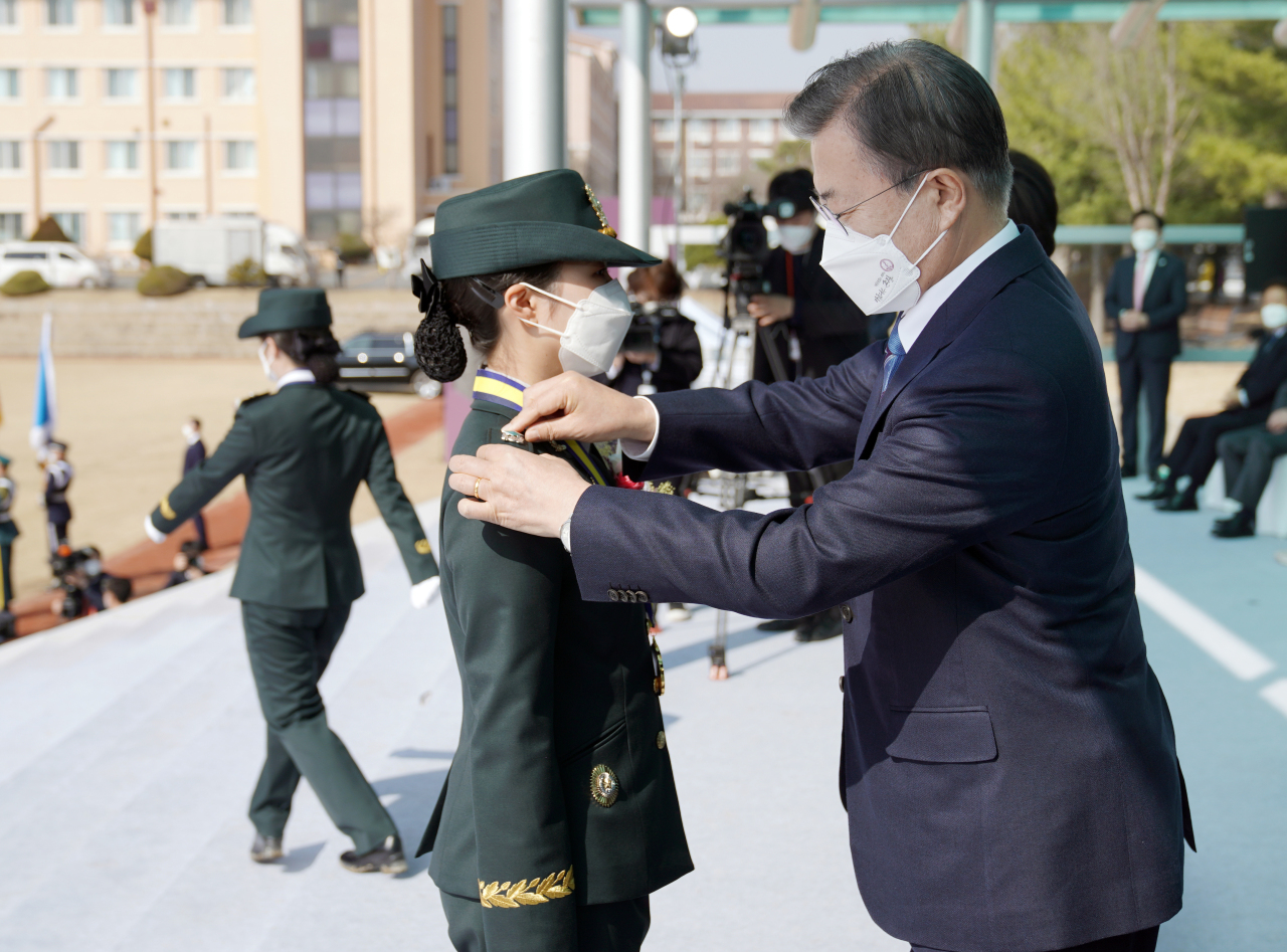 This file photo shows President Moon Jae-in (R) attaching rank insignia on the shoulder of a graduate from Armed Forces Nursing Academy during a ceremony held at its compound in Daejeon, 160 kilometers south of Seoul, last Friday. (Yonhap)