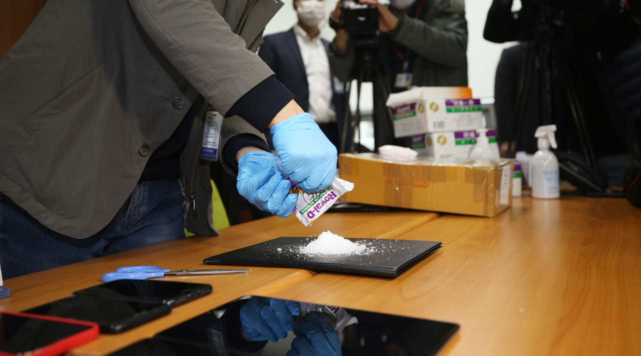 A police officer at the Jeonbuk Police Agency, about 240 kilometers south of Seoul, pours out methamphetamine from a vitamin package on Monday. (Yonhap)