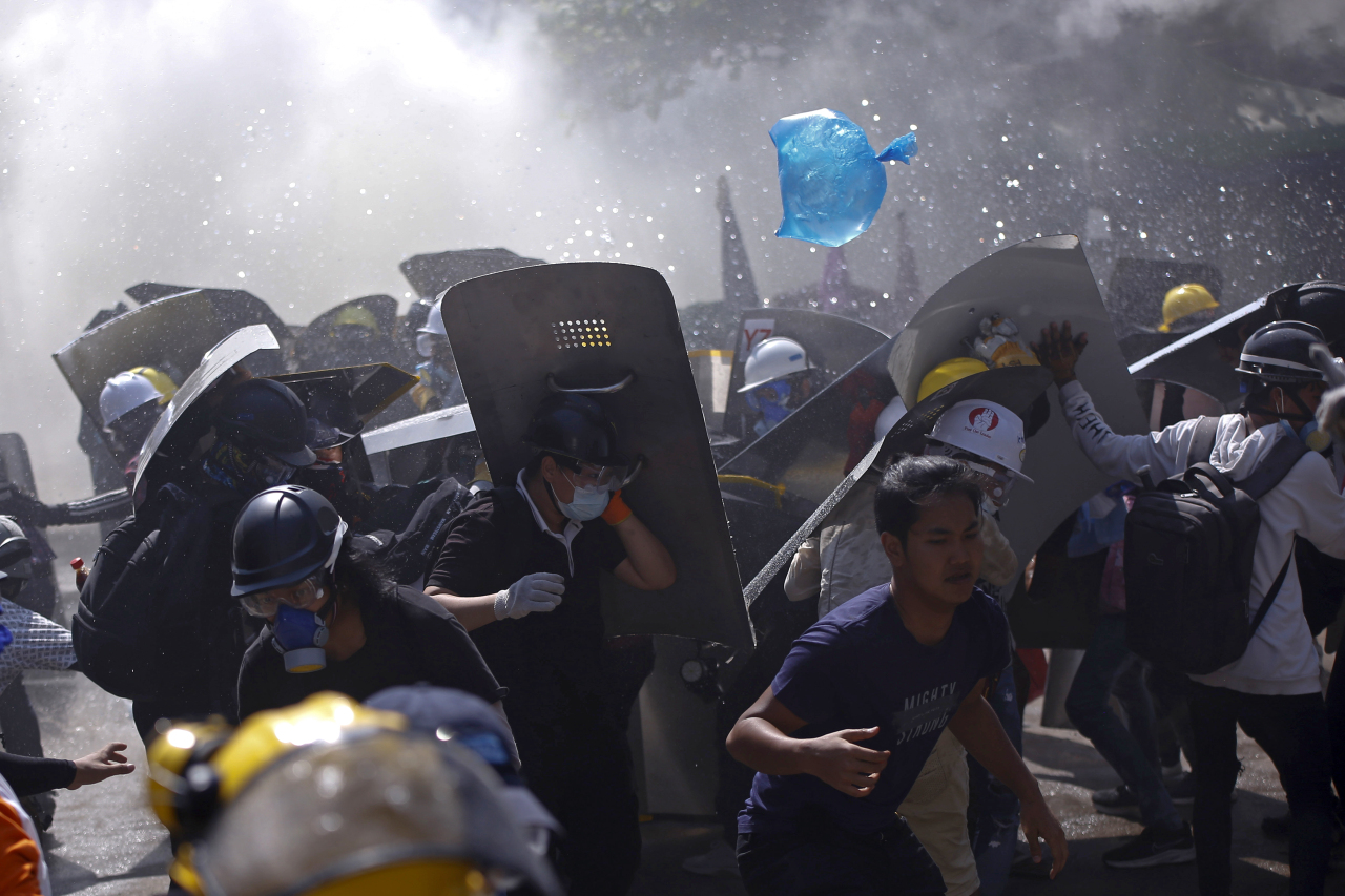 Protesters are dispersed as riot police fire tear gas during a demonstration in Yangon, Myanmar, March 8, 2021. (AP-Yonhap)