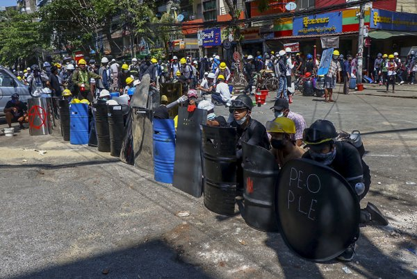 Anti-coup protesters take cover behind makeshift shields during a demonstration in Yangon, Myanmar Thursday, March 4, 2021. (AP-Yonhap)