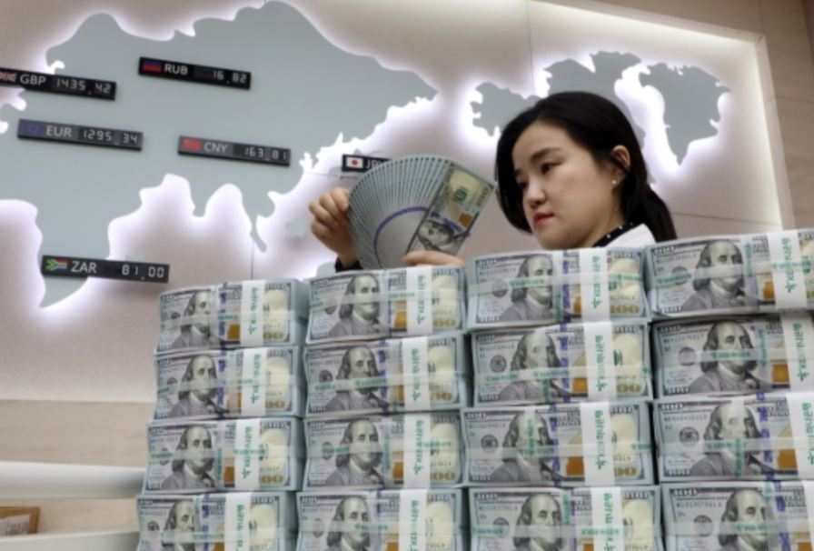 An employee at the headquarters of Hana Bank in Seoul looks into a batch of US dollar bills to single out counterfeits, if any. (Yonhap)
