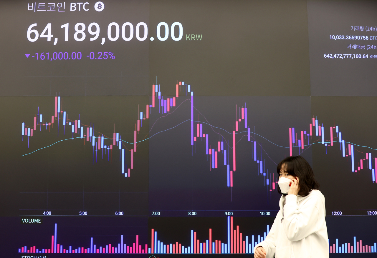 A woman walks past the electronic board of a cryptocurrency exchange in Seoul last Thursday. (Yonhap)