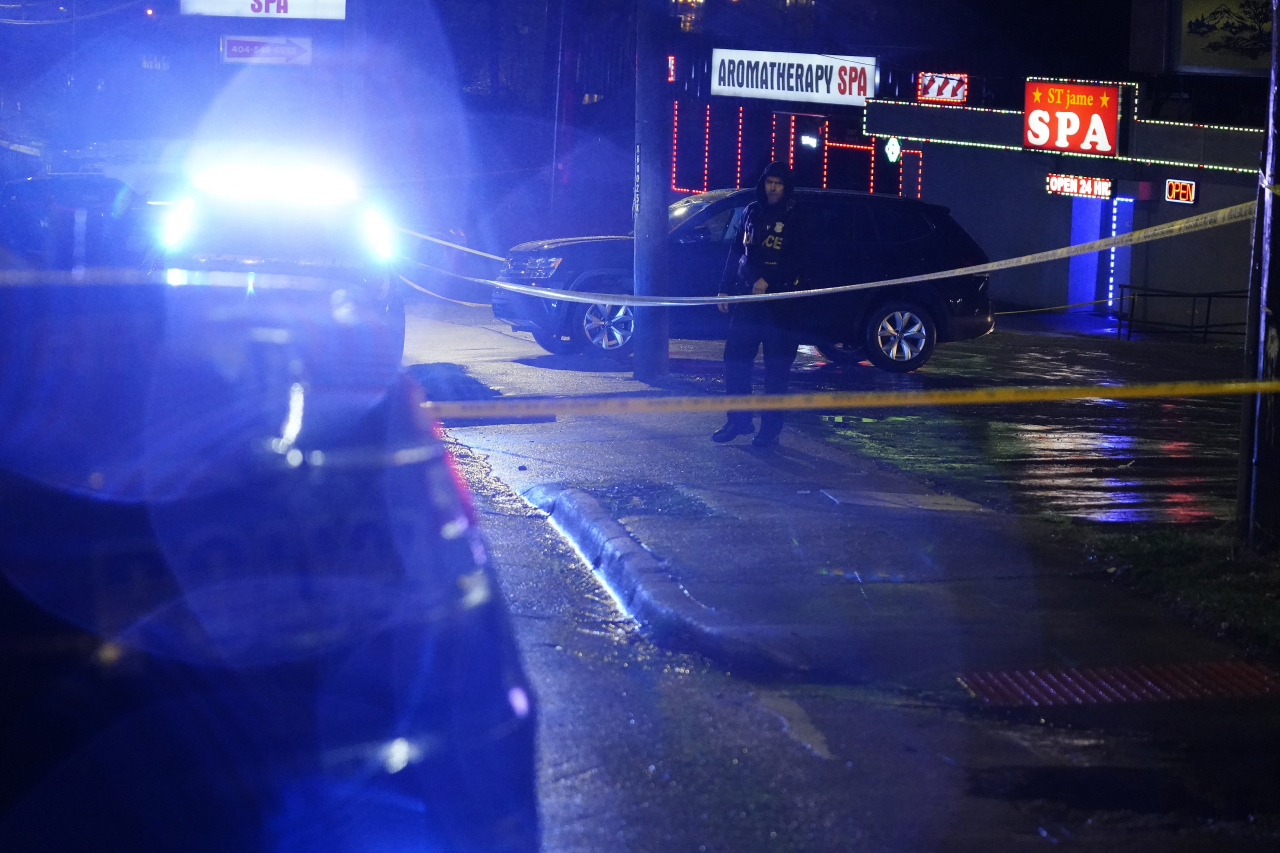 An official stands in front of a massage parlor after a shooting, late Tuesday, in Atlanta. Authorities say shootings at three Atlanta-area massage parlors have left several people dead, many of them women of Asian descent. (AP-Yonhap)