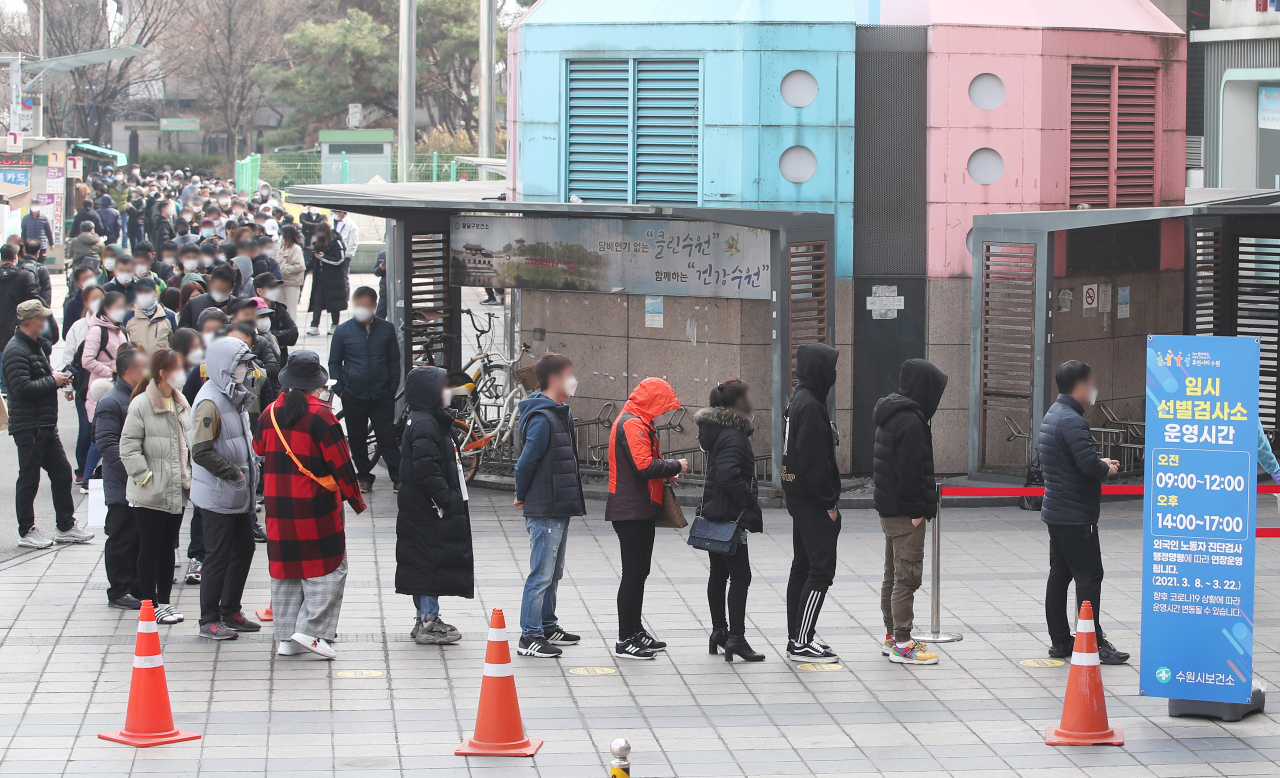 Korean and foreign nationals line up by a testing center in Suwon, Gyeonggi Province, on Sunday as they wait to be diagnosed for COVID-19. (Yonhap)