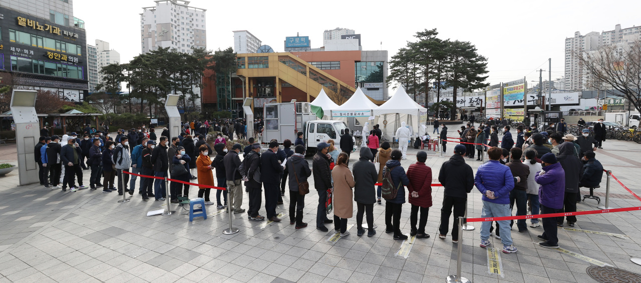 People line up for COVID-19 tests in Guro-gu, Seoul, March 19. (Yonhap)