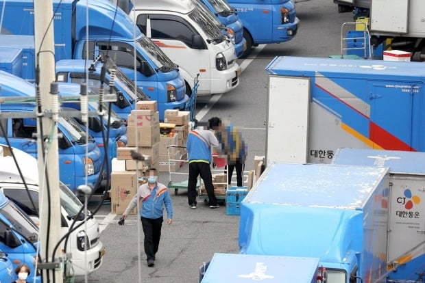 Delivery workers at a logistics center move parcels. (Yonhap)