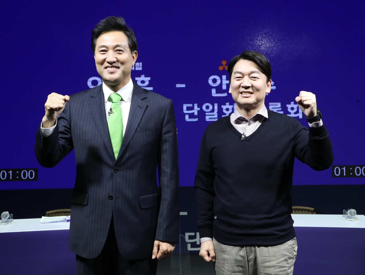 Former Seoul Mayor Oh Se-hoon (L) of the main opposition People Power Party and Ahn Cheol-soo, head of the minor opposition People's Party -- candidates for the April 7 Seoul mayoral by-election -- pose for a photo before a TV debate in Seoul last Tuesday, as part of procedures to unify their candidacies. (Yonhap)