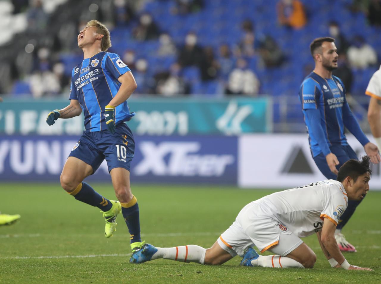 Yoon Bitgaram of Ulsan Hyundai FC (L) reacts to a save by Jeju United goalkeeper Oh Seung-hoon (C) during their K League 1 match at Ulsan Munsu Football Stadium in Ulsan, 415 kilometers southeast of Seoul, last Tuesday. (Yonhap)