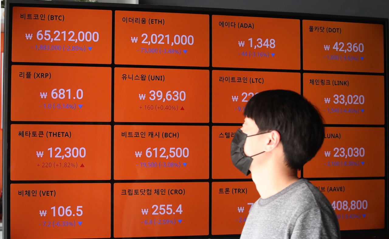 A man looks at a screen that displays cryptocurrency price changes Tuesday morning at the Bithumb Exchange in Seoul. (Yonhap)
