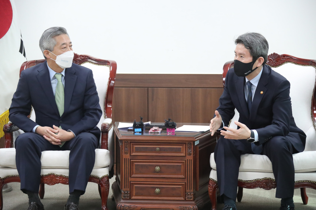 Unification Minister Lee In-young (R) speaks with Lee Ki-bum, head of Korea NGO Council for Cooperation with North Korea (KNCCK), at the start of a meeting on Wednesday. (Yonhap)