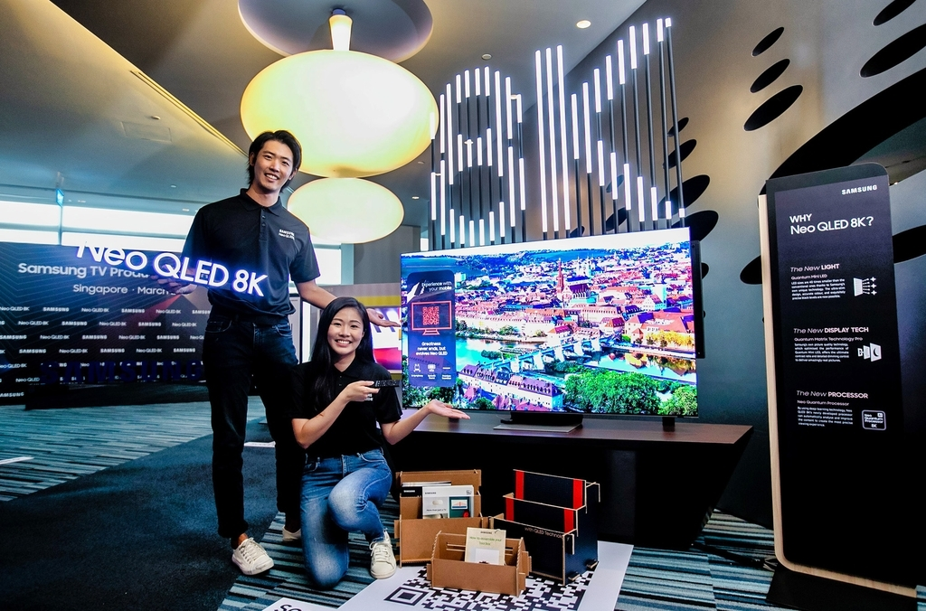 This photo provided by Samsung Electronics Co. on Thursday, shows models promoting Samsung's Neo QLED 8K TV at an event at Mapletree Business City in Singapore. (Samsung Electronics Co.)