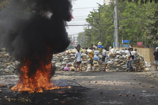 Anti-coup protesters stand beside a burning tire as they fortify their position against the military during a demonstration in Yangon, Myanmar on Tuesday March 30, 2021. (AP-Yonhap)