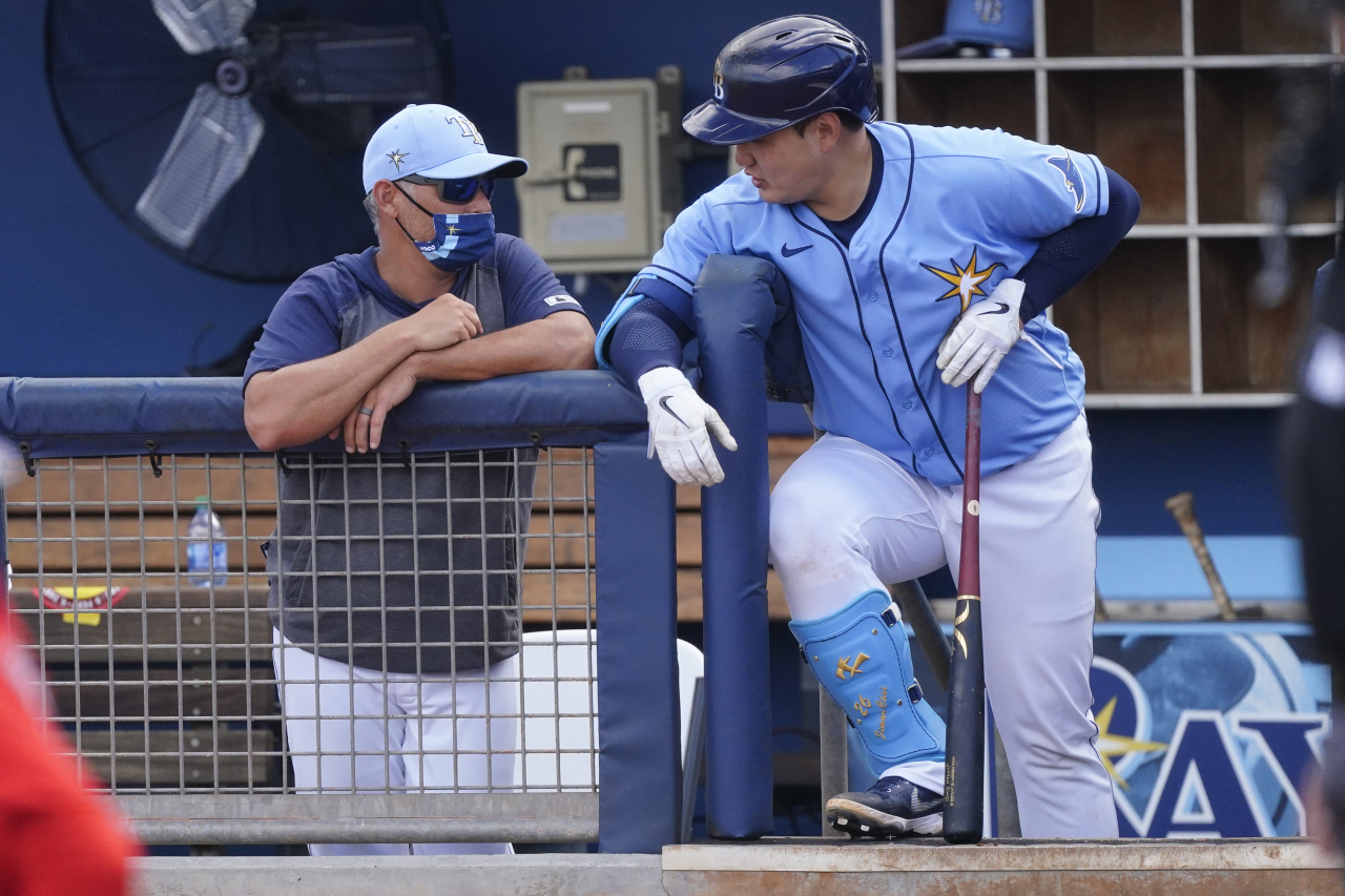In this Associated Press file photo from March 9, 2021, Choi Ji-man of the Tampa Bay Rays (R) chats with his manager Kevin Cash during a major league spring training game against the Boston Red Sox at Charlotte Sports Park in Port Charlotte, Florida. (Yonhap)
