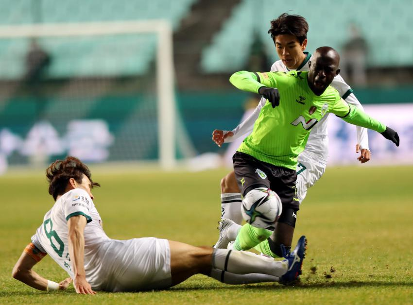 In this file photo from March 9, 2021, Mo Barrow of Jeonbuk Hyundai Motors (R) is tackled by Han Kook-young of Gangwon FC (L) during a K League 1 match at Jeonju World Cup Stadium in Jeonju, 240 kilometers south of Seoul. (Yonhap)