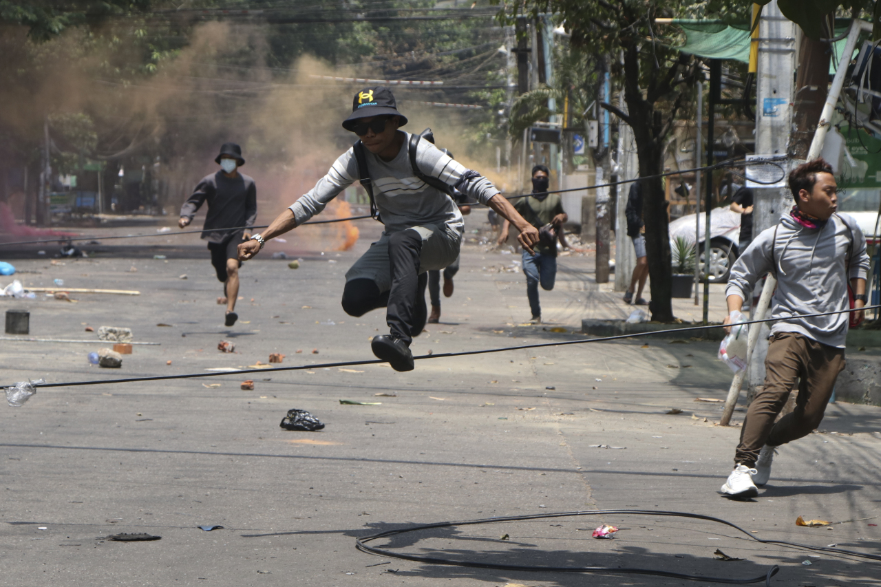 Anti-coup protesters run to avoid military forces during a demonstration in Yangon, Myanmar on Wednesday March 31, 2021. The Southeast Asian nation has been wracked by violence since the military ousted a civilian-led government on February 1 and began to forcibly put down protests. (AP-Yonhap)