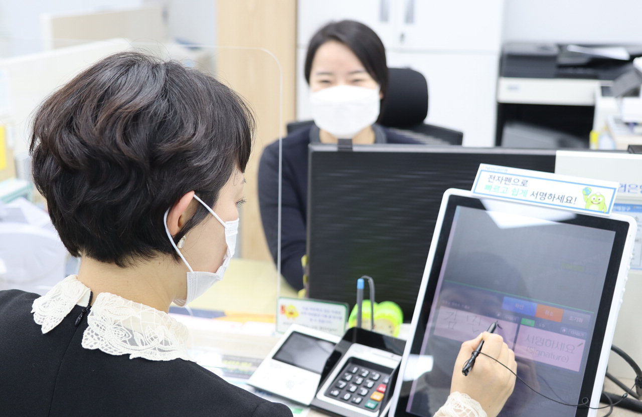 A customer signs documents displayed on a tablet PC installed in a booth at a NH NongHyup Bank branch in Seoul. (NH NongHyup Bank)