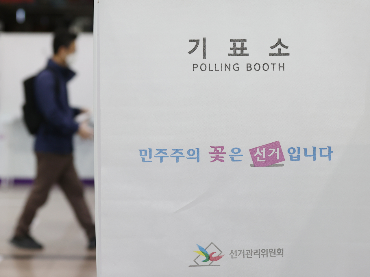 A voter walks toward a polling station at Seoul Station in central Seoul on the first day of the two-day early voting period ahead of the upcoming by-elections on Friday. (Yonhap)