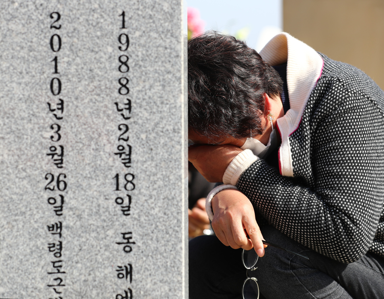A bereaved family member of one of the 46 South Korean sailors killed in the torpedoing of the warship Cheonan by an infiltrating North Korean submarine within South Korean territorial waters in the West Sea on March 26, 2010, sheds tears in front of a grave at the National Cemetery in Daejeon, 164 kilometers south of Seoul, on March 25, 2021, one day ahead of the incident's anniversary. (Yonhap)