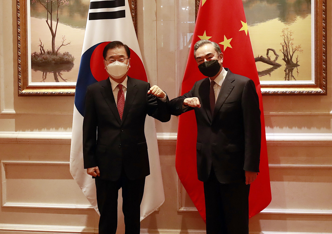 Foreign Minister Chung Eui-yong (L) and his Chinese counterpart, Wang Yi, bump elbows before their talks at a hotel in the southeastern Chinese city of Xiamen on Saturday. (Yonhap)