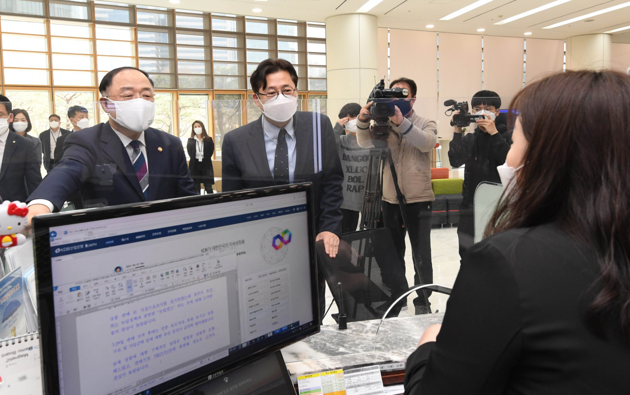 Finance Minister Hong Nam-ki, left, speaks with an employee about the New Deal policy fund at a Korea Development Bank branch in Yeouido, western Seoul on Thursday. (Yonhap)