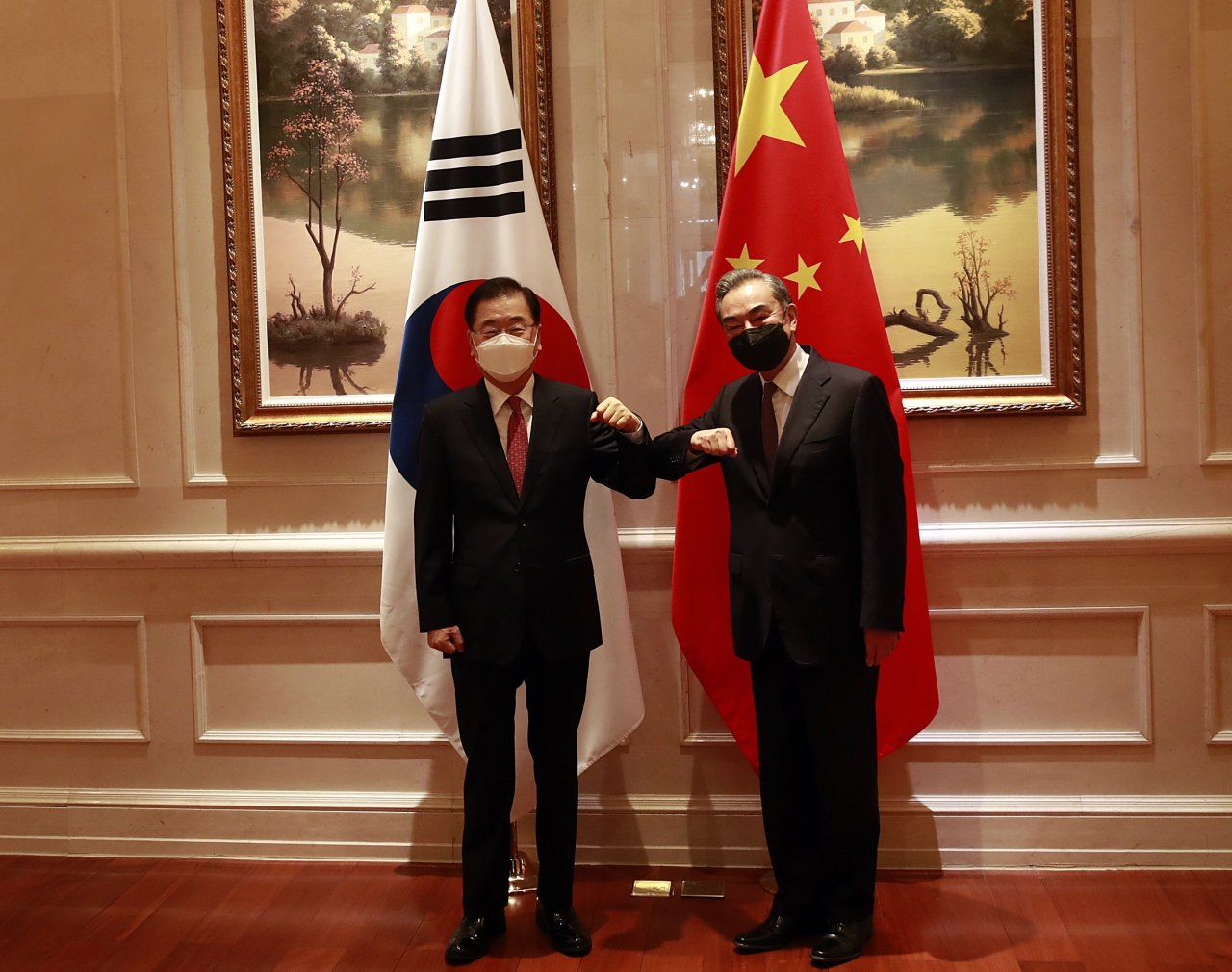 South Korean Foreign Minister Chung Eui-yong (L) and his Chinese counterpart, Wang Yi, bump elbows ahead of their talks in Xiamen, China, on Saturday. (Yonhap)