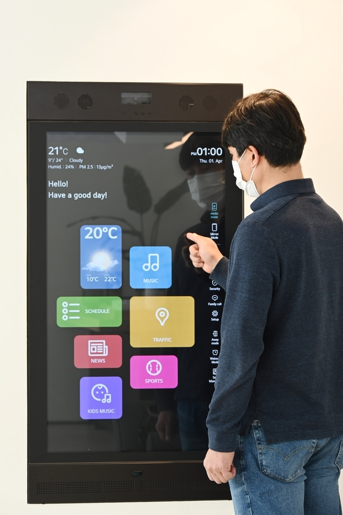 This photo provided by LG Electronics Inc. on Tuesday, shows a researcher from the company checking a smart mirror to use artificial intelligence (AI)-powered services from KT Corp. at LG's smart home in Seongnam, south of Seoul.(LG Electronics Inc.)